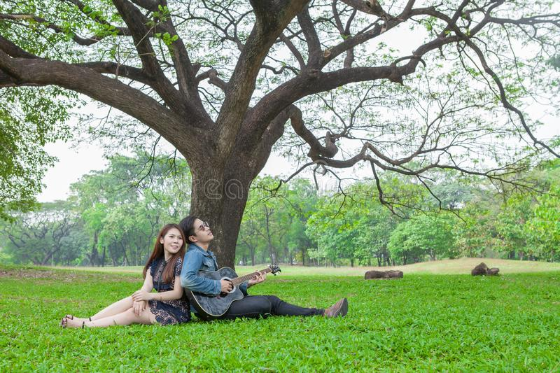 asian young couple in love enjoy playing guitar under a big tree in park stock photos
