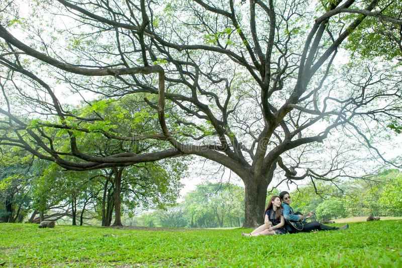 asian young couple in love enjoy playing guitar under a big tree in the park royalty free stock photo