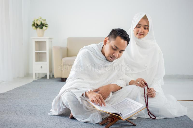 Asian young couple praying with Al-Qur`an and prayer beads. In white traditional clothes stock photos