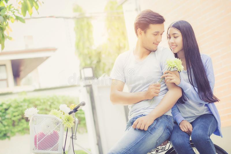 Asian young couple riding on bicycle with happy and fun. At the park with romantic love, activity for leisure, relationship concept royalty free stock image