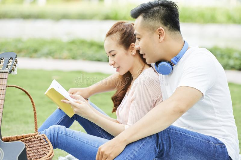 Couple reading book outdoors royalty free stock photography