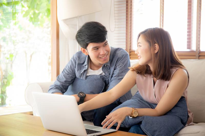 Asian young couple using laptop computer think and searching internet together stock photography