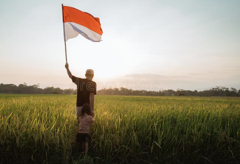 Asian young father with doughter flapping Indonesian flag. Asian young father with daughter flapping Indonesian flag with spirit in the rice field royalty free stock image