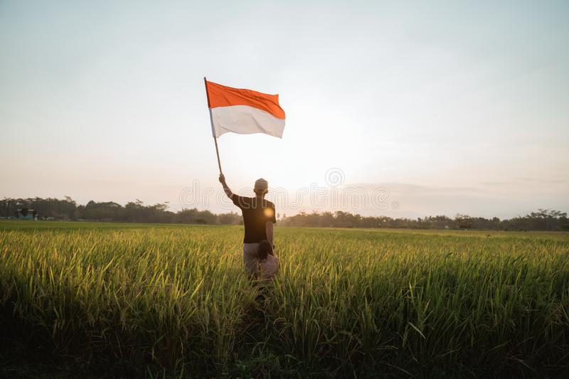 Asian young father with doughter flapping Indonesian flag. Asian young father with daughter flapping Indonesian flag with spirit in the rice field royalty free stock photo