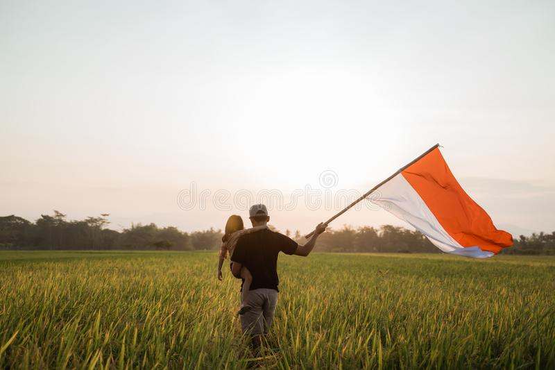 Asian young father with doughter flapping Indonesian flag. Asian young father with daughter flapping Indonesian flag with spirit in the rice field royalty free stock images