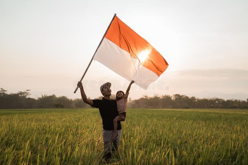 Asian young father with doughter flapping Indonesian flag. Asian young father with daughter flapping Indonesian flag with spirit in the rice field royalty free stock photos