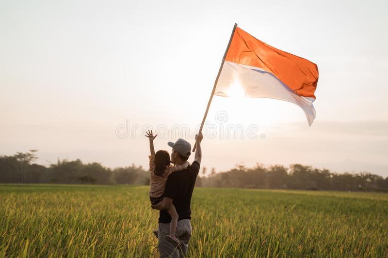 Asian young father with doughter flapping Indonesian flag. Asian young father with daughter flapping Indonesian flag with spirit in the rice field stock photography