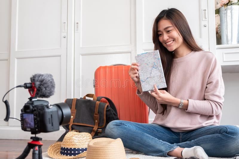 Asian young female blogger recording vlog video with map planning to travel trip at home.online influcencer on social media stock images