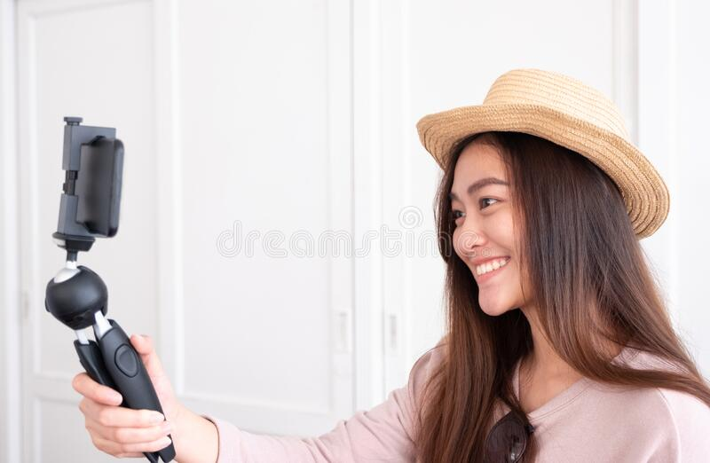 Asian young female blogger recording vlog video with mobile phone live streaming when travel.online influencer on social media stock photography