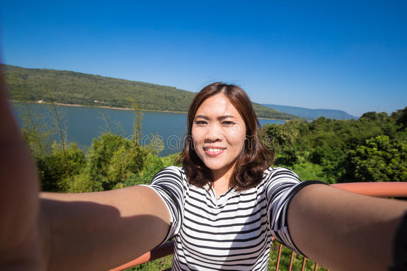Asian young female tourist makes selfie royalty free stock photography