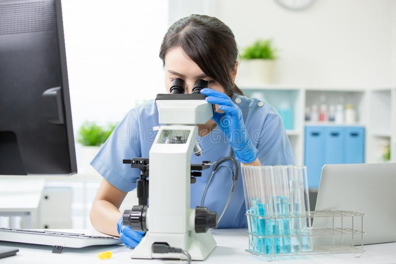 Veterinarian use microscope. Asian young femalie veterinarian check illness with microscope royalty free stock photos