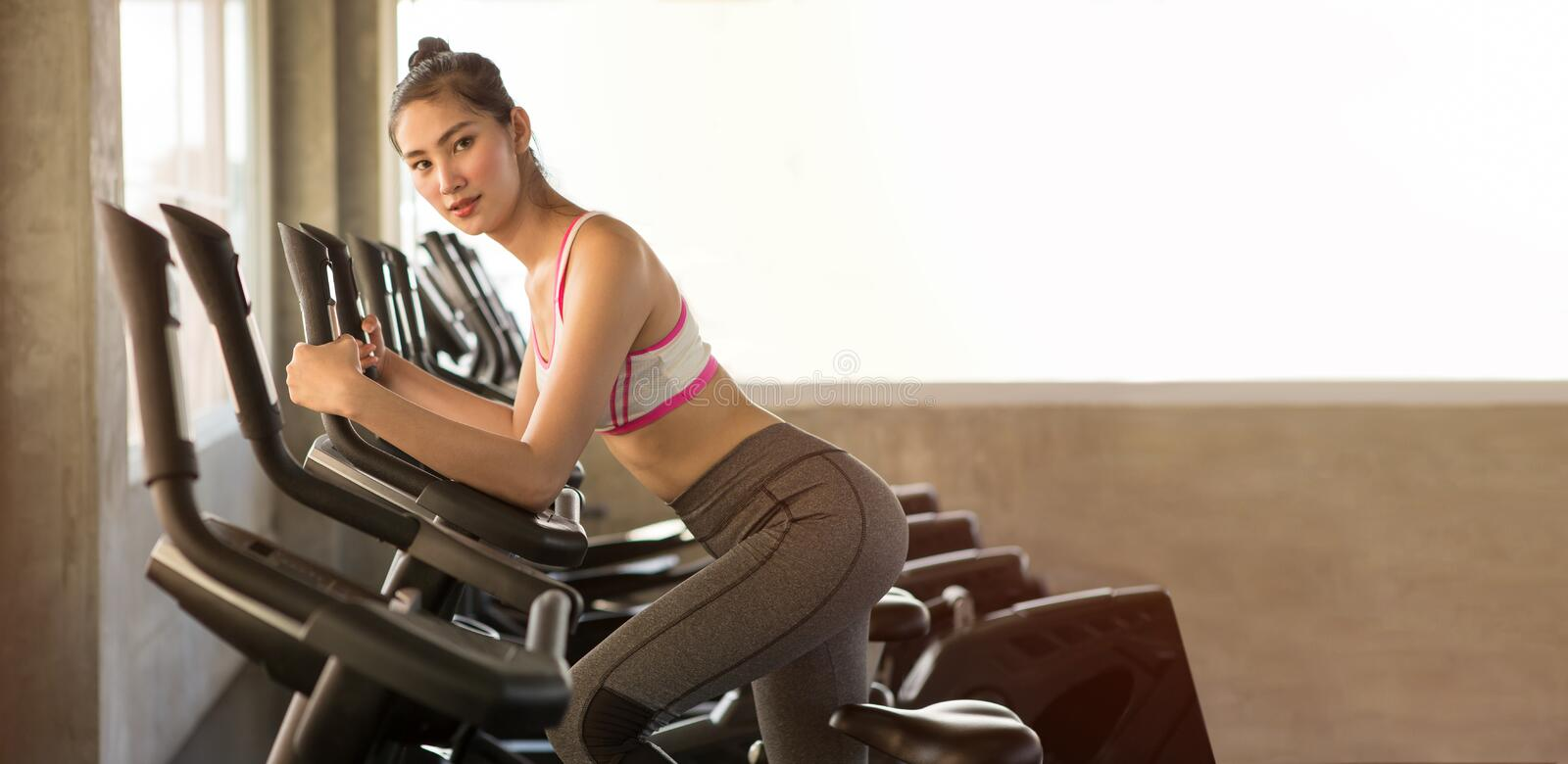 Asian young fitness woman in sportswear exercising with biking in sport gym club . girl workout on bike machine . panorama copy. Space royalty free stock photo
