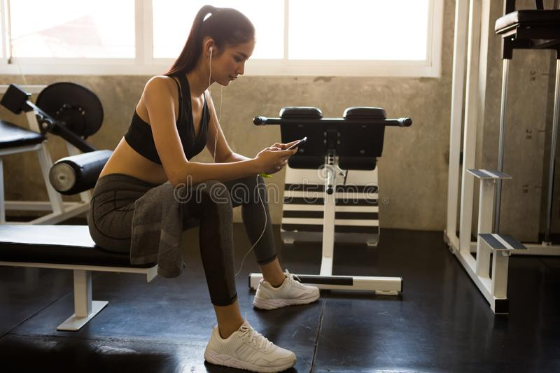 asian young fitness woman in sportswear with towel using mobile smart phone and listening music with earphones relaxing sitting stock photography