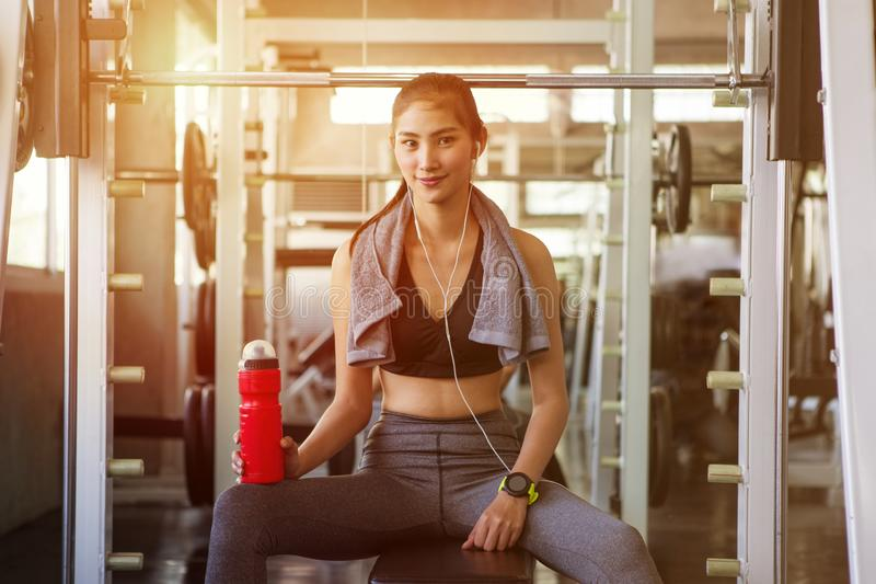 asian young fitness woman with towel listening music with earphones holding water bottle relaxing sitting on Weight lifting royalty free stock photography