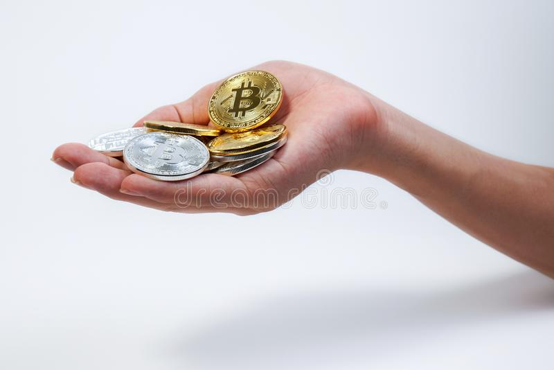 Asian young hand holding up many golden bitcoin and silver bitcoin in two hand. Close up of bitcoin in open hand isolated on white royalty free stock images