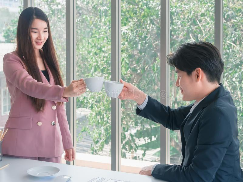 Asian young handsome businessman and beautiful business woman greetings by coffee royalty free stock image