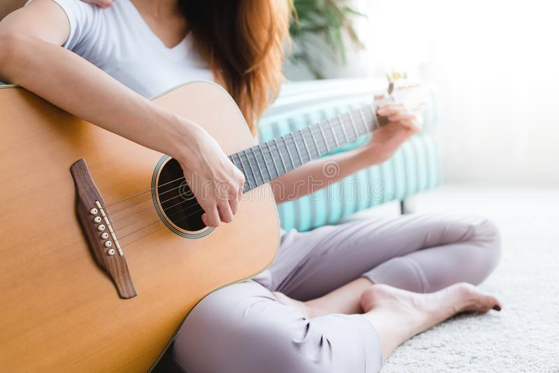 Asian young lesbian couple playing guitar for her lover with love moment in the bedroom surrounded with warm sunlight. stock images