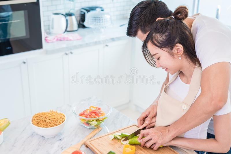 Asian young lovers or couples cooking breakfast in the morning i. N kitchen room. Man teaching women to slice vegetable and rice. Relationship and Family concept stock image