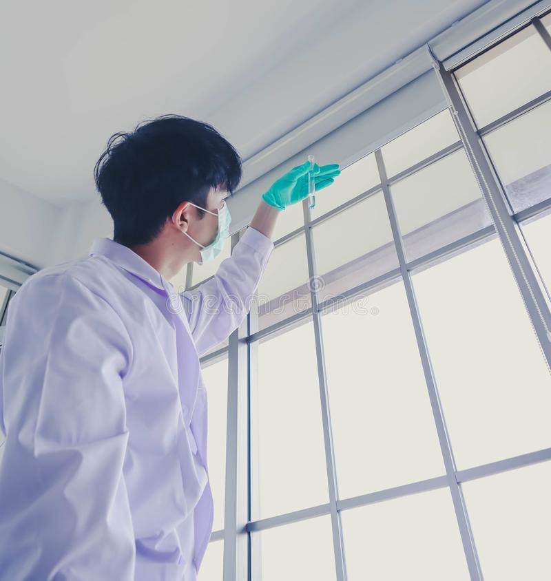 Asian young male scientist examiming and analysis the sample of blue liquid in the tube in laboratory royalty free stock photo