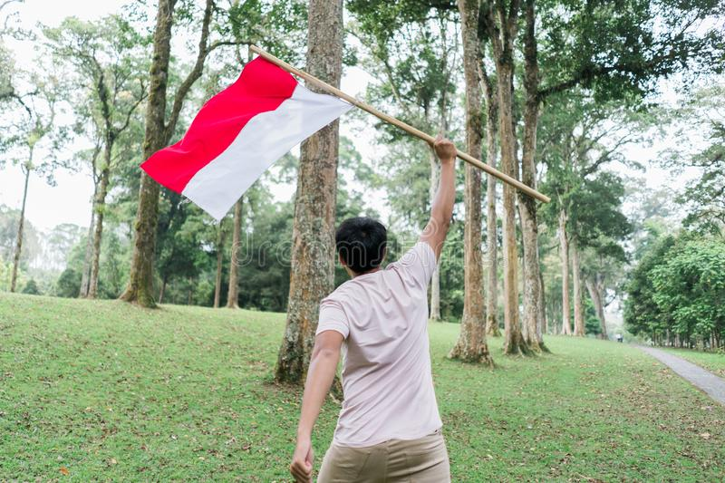Asian young man flapping Indonesian flag. With spirit in the park stock photo