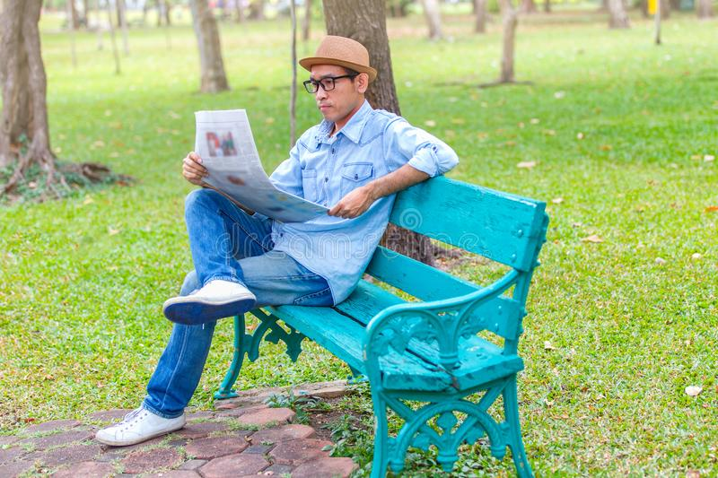 Asian young Man with hat sitting on a wooden bench and reading a newspaper in a park stock photo