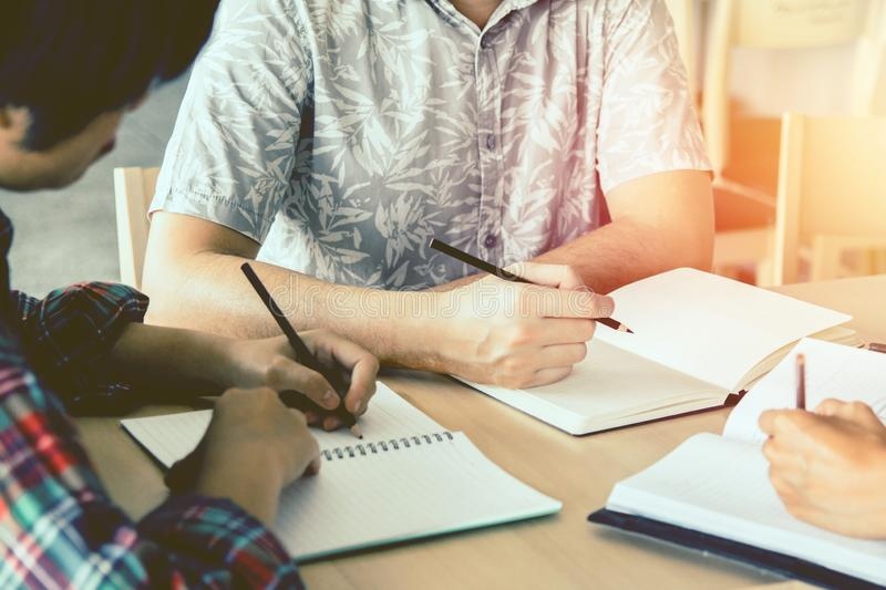 Asian young man,Homosexuality or woman sitting pointing studying examining. Tutor books. With friends. Young students campus helps friend catching up and royalty free stock photography