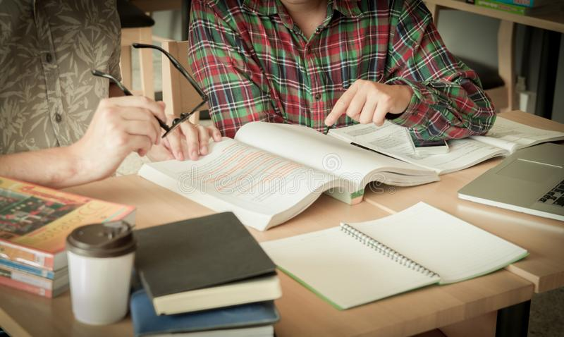 Asian young man,Homosexuality or woman sitting pointing studying examining. Tutor books with friends. Young students campus helps friend catching up and stock image