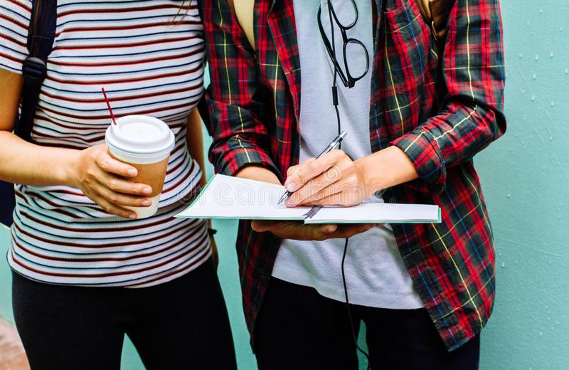 Asian young man,Homosexuality or woman standing pointing studying examining. Tutor books with friends. Young students campus helps friend catching up and stock photography