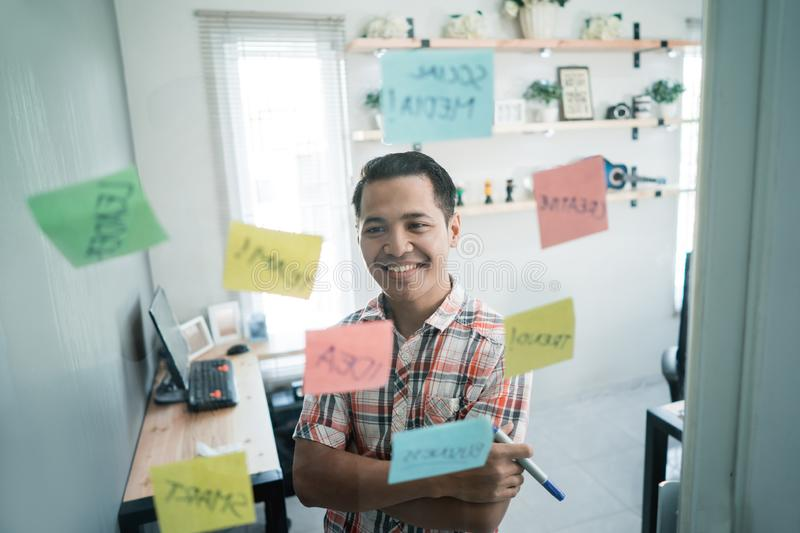 Asian young man look at the paper and think of some good ideas. To make it happen royalty free stock image