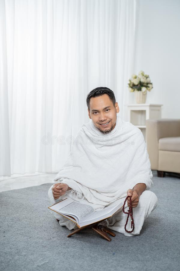 Asian young man praying with Al-Qur`an and prayer beads. In white traditional clothes royalty free stock photo