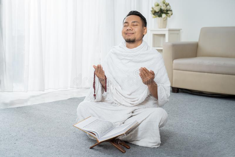 Asian young man praying with Al-Qur`an and prayer beads. In white traditional clothes stock images