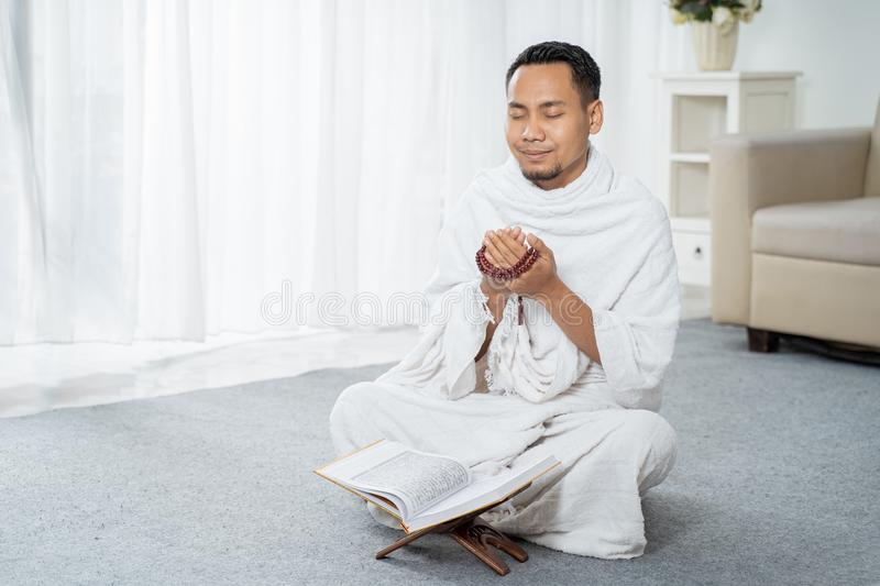 Asian young man praying with Al-Qur`an and prayer beads. In white traditional clothes stock photos