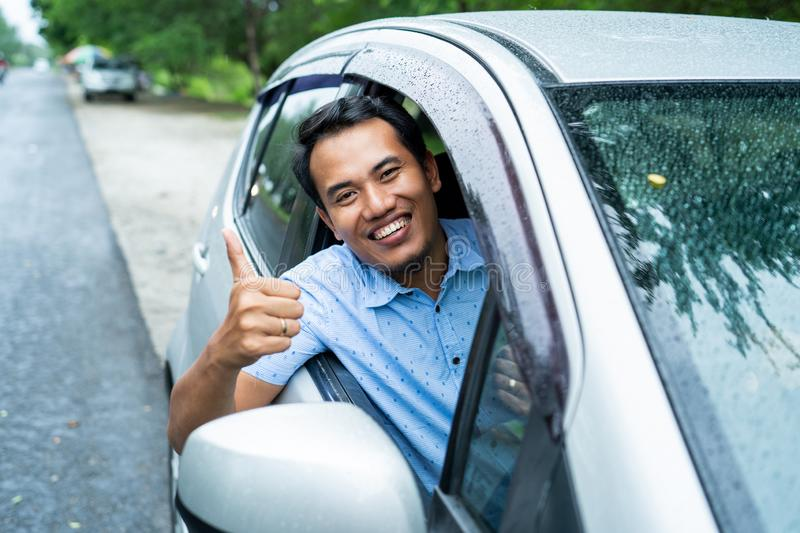 Asian young man ride car and showing thumb up stock images