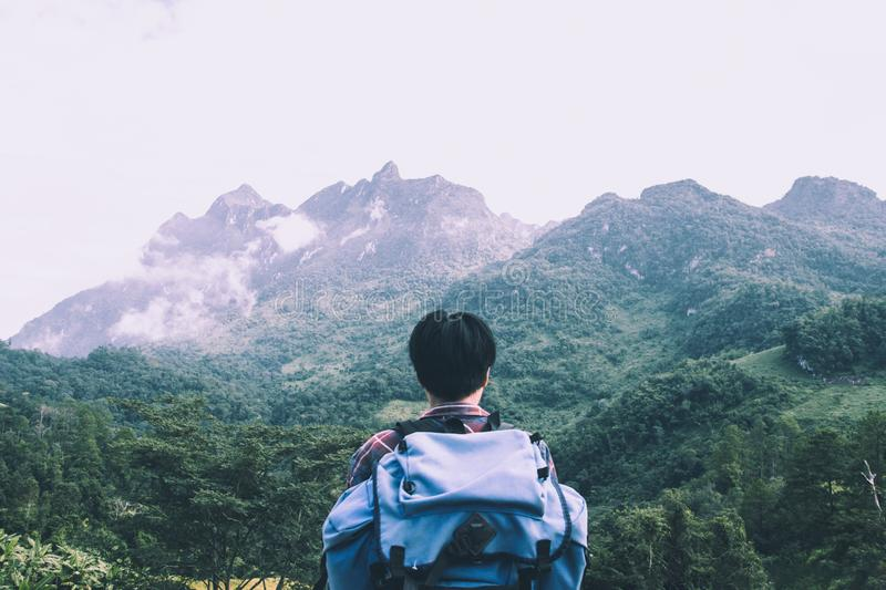 Asian young man in Scottish shirt and black hat hiking at mountain peak above clouds and fog Hiker outdoor. Doi Luang Chiang Dao C royalty free stock photo