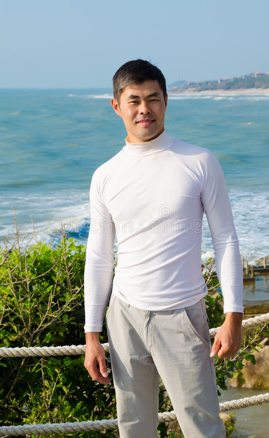 Asian young man by sea royalty free stock photo