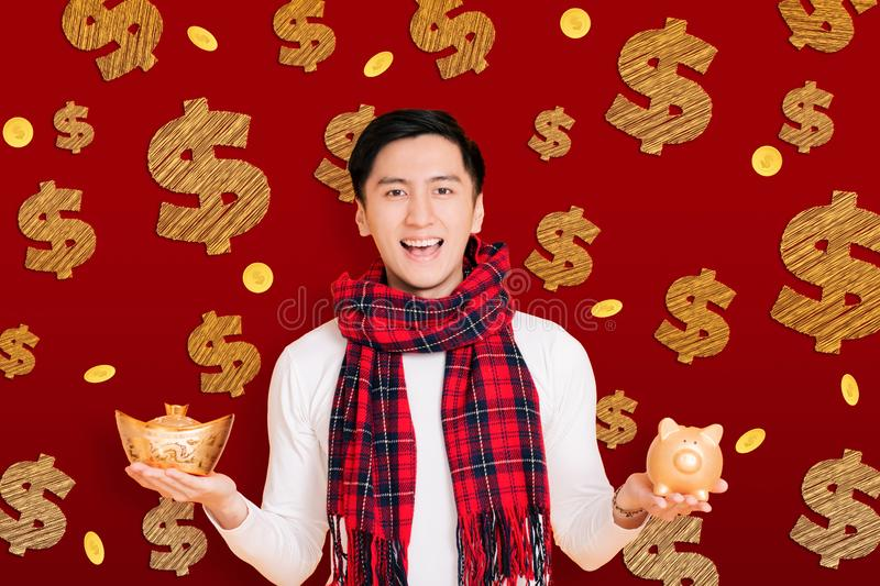 Asian young man showing the gold piggy bank celebrating for chinese new year.  royalty free stock image