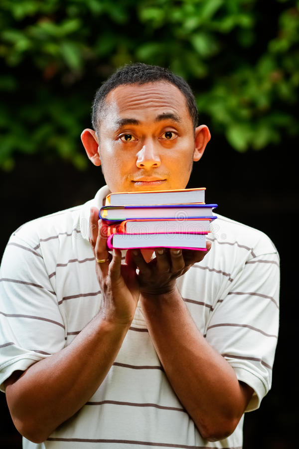 Download Asian Young Man With Stack Of Books On Hands Stock Image - Image of school, knowledge: 24045671