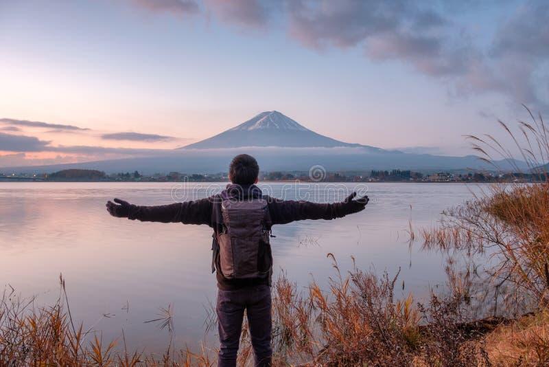 Asian young man stand looking Mount Fuji on Kawaguchiko Lake at stock images