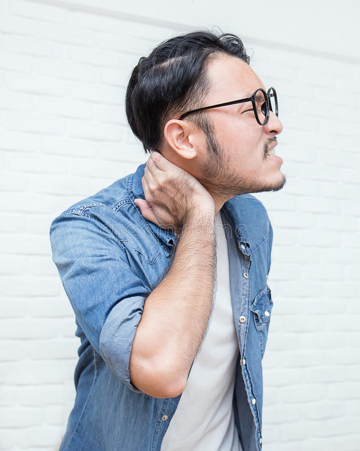 Asian young man suffering from pain in his neck royalty free stock image