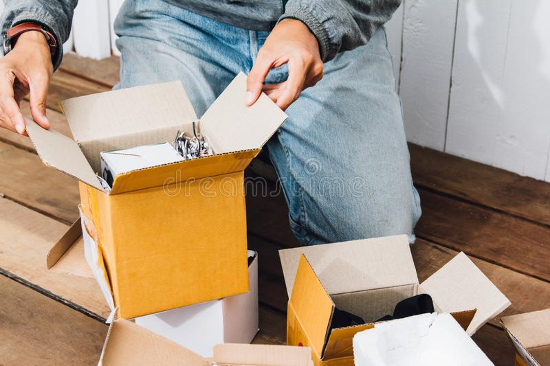 Asian young man Unpack the postal box,parcel while He was surprised and happy sitting on Wooden floor at home.  royalty free stock photography