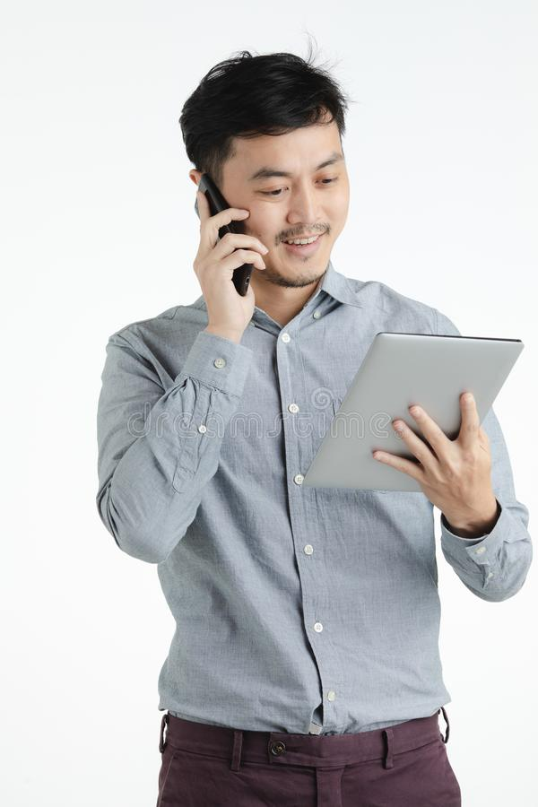 Asian young man using tablet and smartphone royalty free stock photography