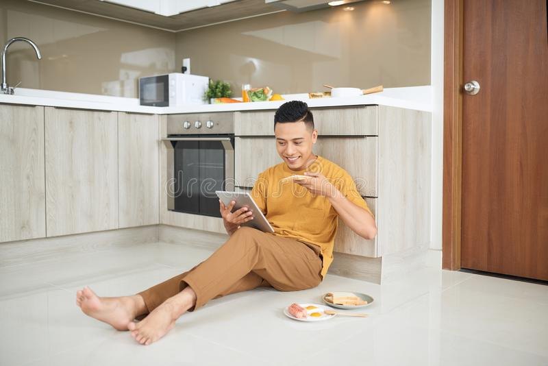 Asian young man work at home, an owner of online business, eating .sausage and looking on tablet royalty free stock image