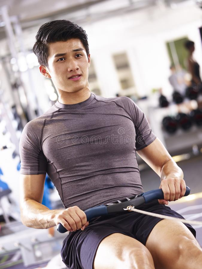 Asian young man working out on rowing machine royalty free stock photography