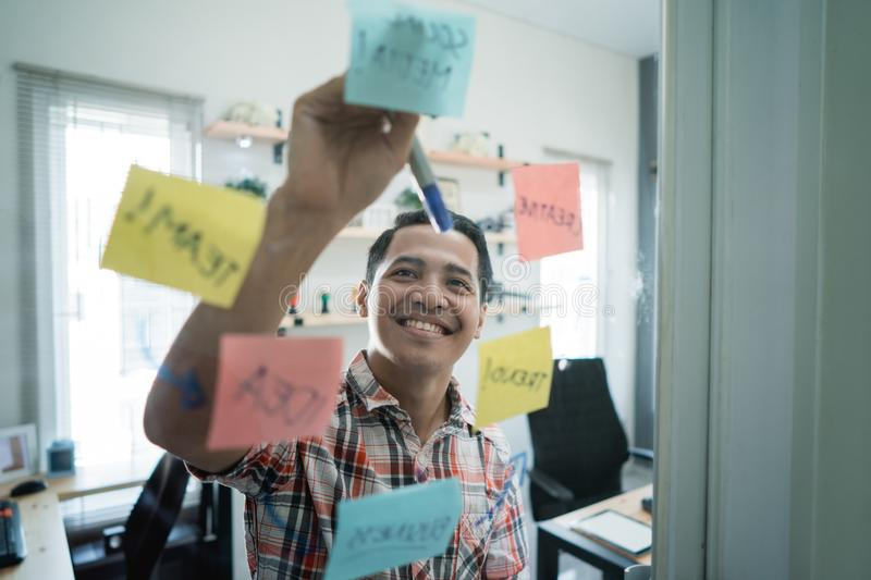 Asian young man wrote some flowchart model word. To make office meeting material royalty free stock photos