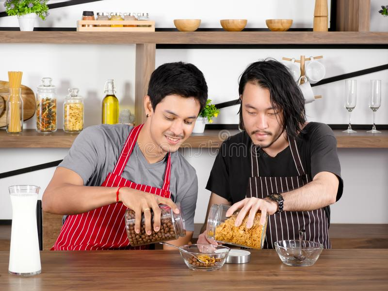Asian young men wear apron are pouring cereal into a glass bowl together on wooden table. royalty free stock photo