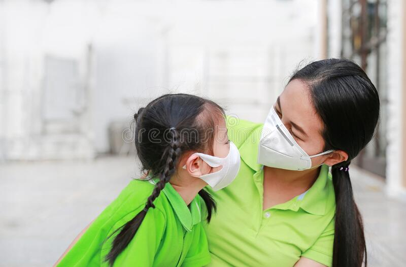 Asian young mother and her daughter wearing protective mask while outside to against PM 2.5 air pollution in Bangkok city. royalty free stock photo