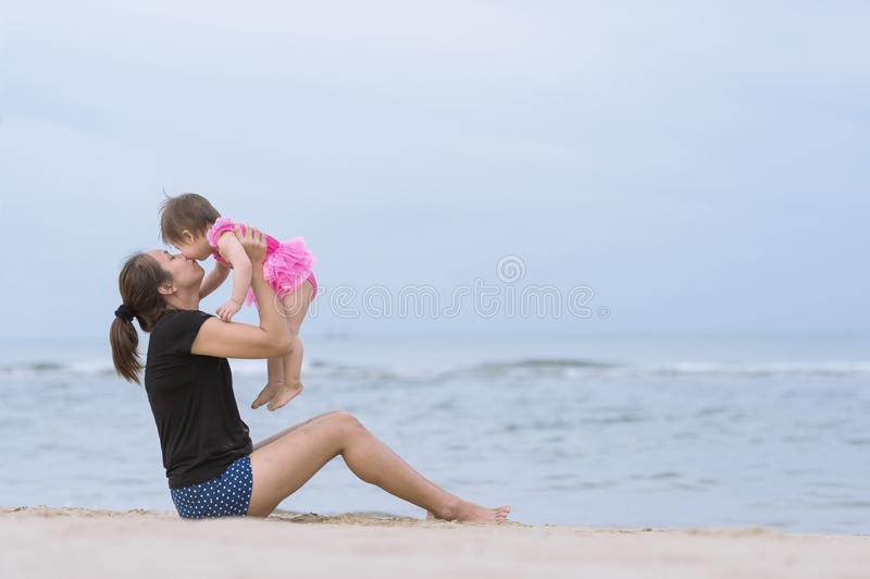 Asian young mother throwing up her baby girl on sandy beach royalty free stock photos