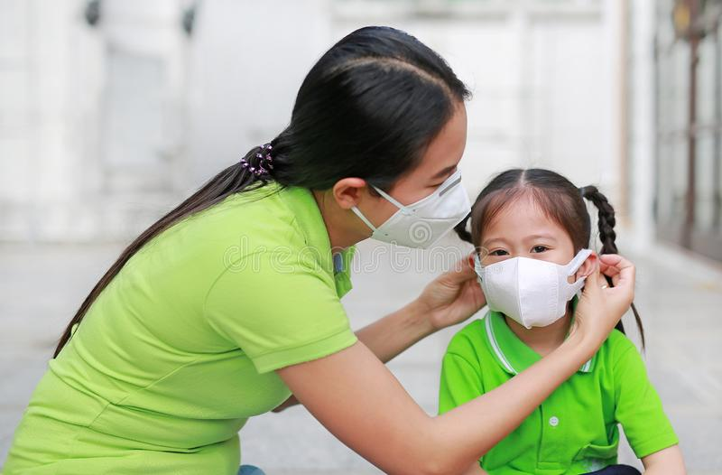 Asian young mother wearing protective mask for her daughter while outside to against PM 2.5 air pollution in Bangkok city. Thailand royalty free stock photos