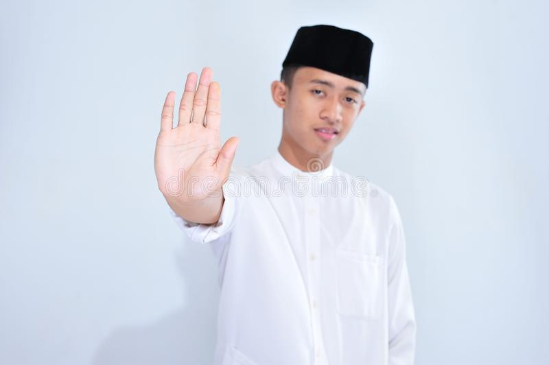 Asian young muslim man with open hand doing stop sign with serious and confident expression, defense gesture stock photos