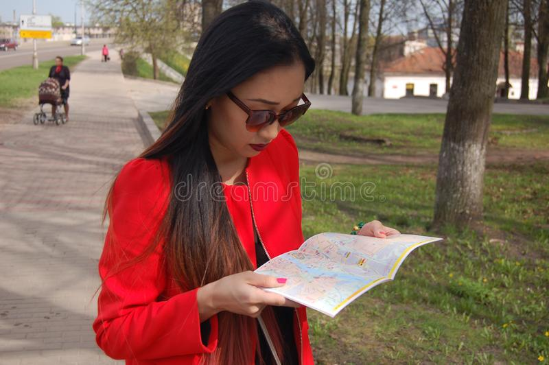 Asian young pensive girl in sunglasses looking at a guide map royalty free stock photos